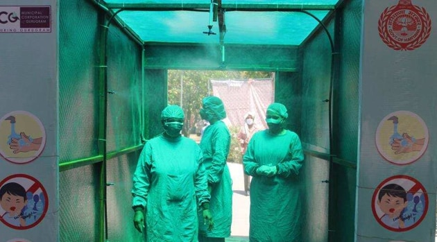 Medical staff in protective gear walk through a disinfecting tunnel outside Civil Hospital Sector 10 of Gurugram.(Yogendra Kumar/HT PHOTO)