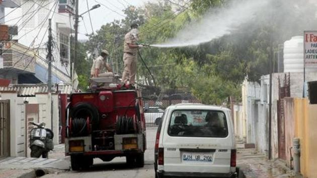 Municipal workers spray disinfectant on day 7 of national lockdown imposed to curb the spread of coronavirus in Jaipur, Rajasthan, India, on Tuesday, March 31, 2020.(Himanshu Vyas / Hindustan Times)