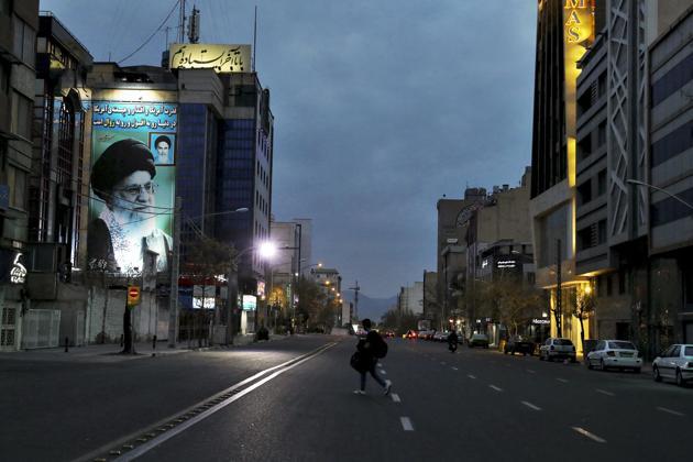 A pedestrian crosses an empty street with a portrait of Iran's Supreme Leader Ayatollah Ali Khamenei, in Tehran, Iran.(AP photo)