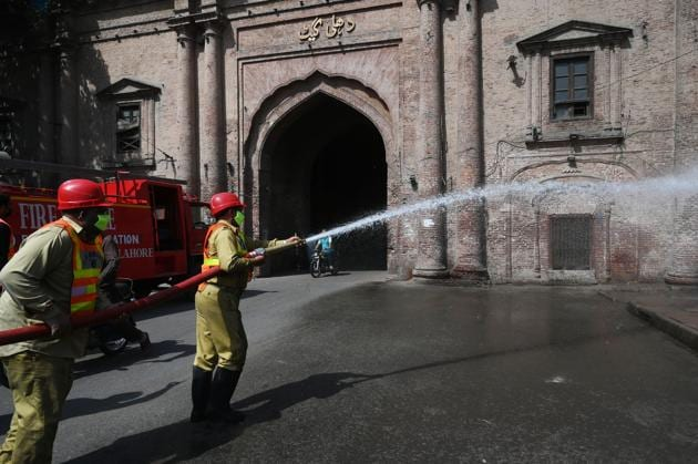 Municipal workers disinfecting a street in Lahore's old city on March 23, 2020.(Arif Ali/AFP)