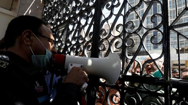 FILE PHOTO: A police officer uses a megaphone, requesting people to go and pray at home, at the locked entrance gate of a mosque during a lockdown after Pakistan shut all markets, public places and discouraged large gatherings amid an outbreak of coronavirus disease (COVID-19), in Karachi, Pakistan March 27, 2020.(REUTERS)