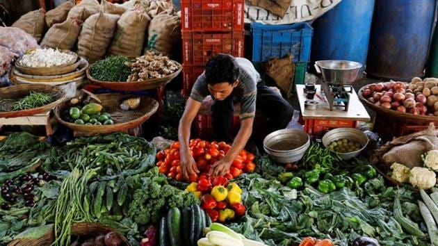 Covid-19: A vendor sorts tomatoes as he waits for customers at a vegetable market in Mumbai. Movement of primary articles, such as grains and vegetables, as well as other essential goods have continued to stumble.(REUTERS)