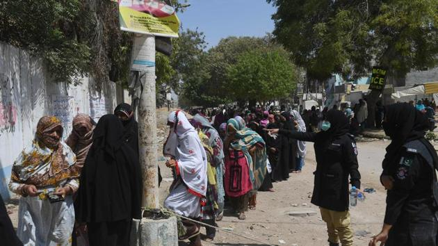 Policewomen keep watch as women wait to collect cash through a bank under the Pakistan governmental Ehsaas Emergency Cash Programme for families in need during a government-imposed nationwide lockdown as a preventive measure against the COVID-19 coronavirus, in Karachi on April 13, 2020. (Photo by Asif HASSAN / AFP)(AFP / Photo used for representational purpose only)