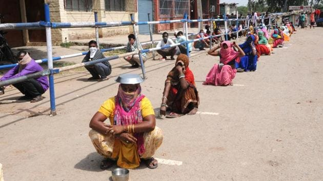 People waiting in a queue for food in the heat of noon in colony no 4 of Industrial Area Phase 1, Chandigarh, amid the curfew on Wednesday.(Keshav Singh/HT photo)