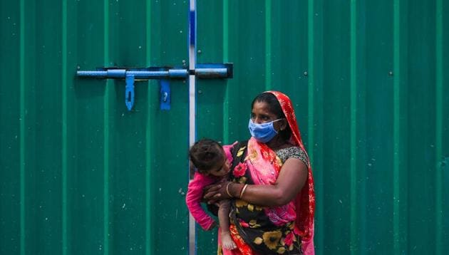 A woman holds her baby as she waits to collect food at Safdarjung Enclave during lockdown, in New Delhi, India, on Tuesday, April 14, 2020.(Amal KS/HT PHOTO)