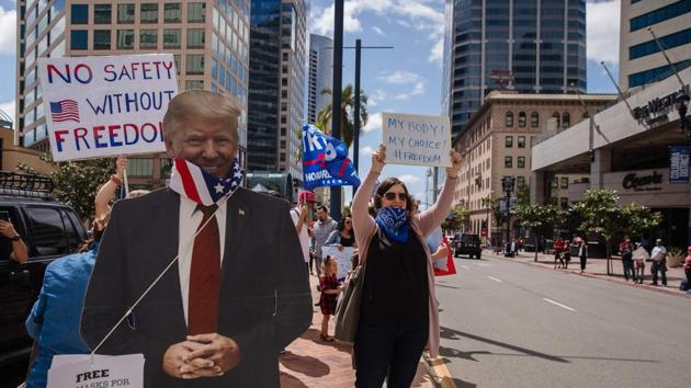 A Trump cutout with a US flag around its neck is seen next to protesters rallying in downtown San Diego against California's stay at home order. Hundreds protested Saturday in cities across America against coronavirus-related lockdowns -- with encouragement from President Donald Trump -- as resentment grows against the crippling economic cost of confinement.(AFP)