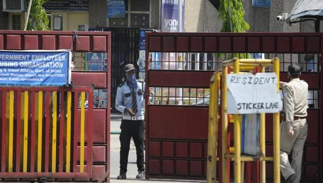 A security personnel closing the entrance gate at Kendriya Vihar after it was marked as a sensitive zone by the administration in wake of the coronavirus outbreak, during lockdown, at Sector 82, in Noida.(Sunil Ghosh / Hindustan Times)
