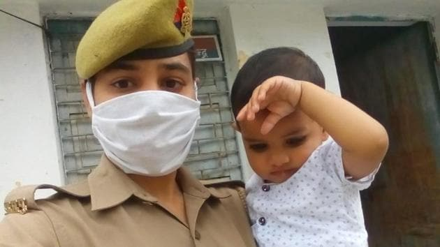 Police officer Chitralekha on duty with her one-year-old child.