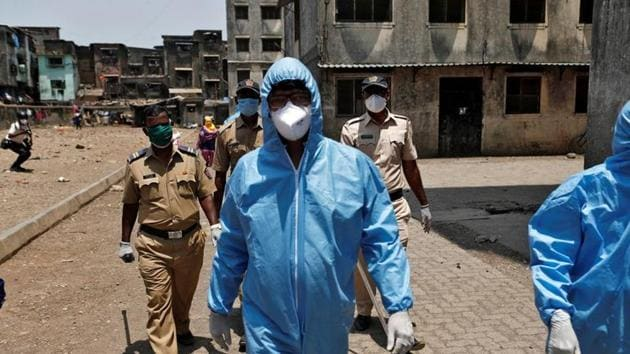 Health workers wearing hazmat suits and masks are accompanied by police officers as they conduct an inspection in a residential area, during a nationwide lockdown in India to slow the spread of COVID-19, in Dharavi, Mumbai.(REUTERS)
