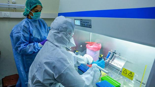 Medics at the real-time Polymerase Chain Reaction laboratory (PCR lab) at the Kalamassery Medical College Hospital in Kochi.(PTI)