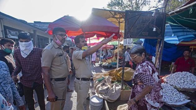 Police personnel urge vendors around Mahatma Phule Market to shut roadside stands to avoid crowd amid Coronavirus scare Pune, India, on March 19, 2020.(Pratham Gokhale/HT Photo)