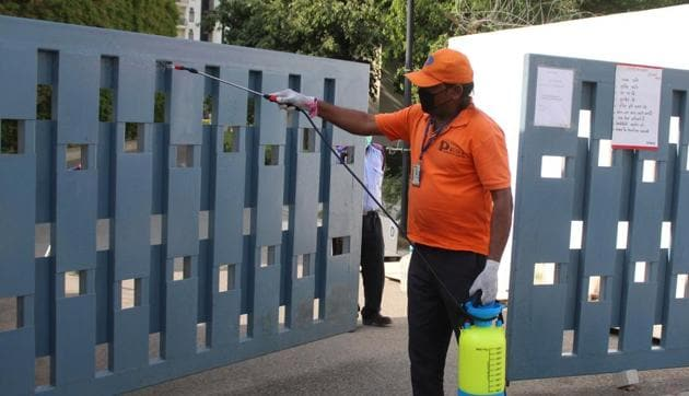 Gurugram, India- April 21: A Grand Arch staff member chemically disinfects the entrance gate during lockdown against coronavirus, at The Grand Arch, Sector 58, in Gurugram, India, on 21 April 2020.(Yogendra Kumar/HT PHOTO)