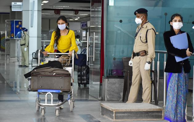 Passengers and CISF personnel seen wearing face masks as a precautionary measure amid rising coronavirus concerns, at Sri Guru Ram Das Jee International Airport, in Amritsar. (Photo by Sameer Sehgal/Hindustan Times)