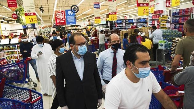 Majid Al Futtaim CEO Alain Bejjani, center left, and store manager Arnaud Bouf, center, walk through heavy shopping traffic during the coronavirus pandemic in the world's busiest Carrefour supermarket, at the Mall of the Emirates in Dubai, United Arab Emirates.(AP)
