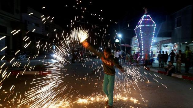 A Palestinian boy waves a homemade sparkler firework as he celebrates ahead of the holy fasting month, amid concerns about the spread of the coronavirus disease (COVID-19), in the southern Gaza Strip.(REUTERS)