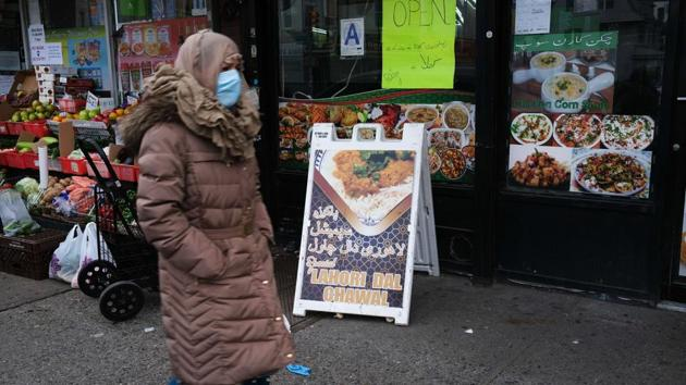 A woman walks through a neighbourhood with numerous halal restaurants and groceries on the eve of the Muslim Ramadan holiday on April 23, 2020 in New York City.(AFP)