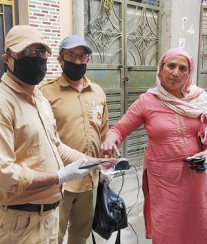 A pensioner registering her thumb impression on a biometric device in Ludhiana on Sunday.(HT Photo)