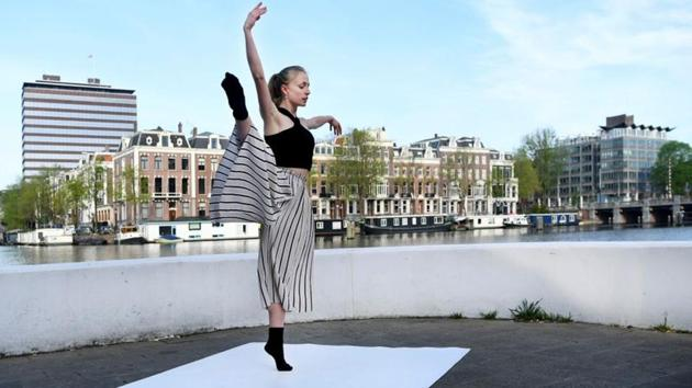"""Ballet dancer Yvonne Slingerland Cosialls of the Dutch National Ballet performs on the streets of Amsterdam for the """"Gently Quiet"""" project, amid the coronavirus disease (COVID-19) outbreak, in Amsterdam, the Netherlands April 24, 2020. REUTERS/Piroschka van de Wouw(REUTERS)"""