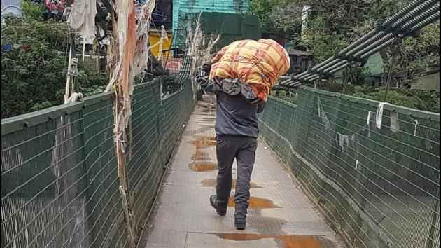 A Nepalese man crosses a bridge in Dharchula in Uttarakhand to enter Nepal on Thursday.(HT PHOTO)