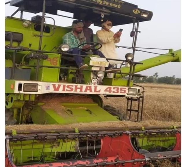 A postman providing money to a farmer reaping his crop on a combine machine in Hisar.(HT PHOTO)