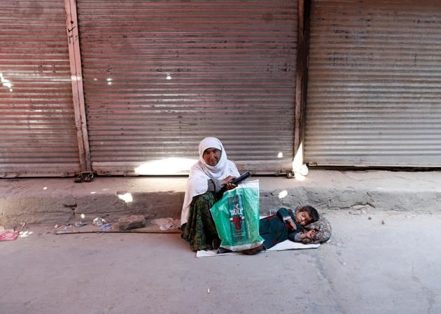 An Afghan woman with a child waits for alms in front of closed shops during the coronavirus disease (COVID-19) outbreak in Kabul, Afghanistan April 23, 2020. REUTERS/Mohammad Ismail(REUTERS)