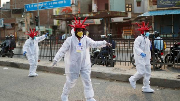 Artists wearing coronavirus-shaped helmets and protective suits walk on a street as they request people to stay at home during an extended lockdown to slow the spread of the coronavirus disease (COVID-19) in New Delhi.(REUTERS)