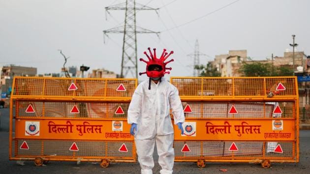 An artist wearing a coronavirus-shaped helmet and a protective suit stands next to a police barricade as he requests people to stay at home during Covid-19 lockdown in New Delhi on April 30.(Reuters Photo)