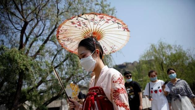 A woman wearing face mask and traditional Chinese clothing visits Gubei Water Town on the first day of the five-day Labour Day holiday, following the coronavirus disease (Covid-19) outbreak, on the outskirts of Beijing, China.(REUTERS)