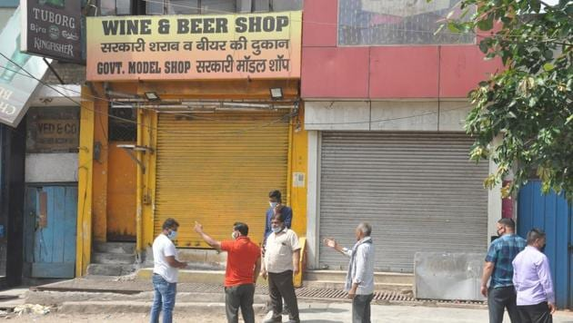 People seen outside a shuttered liquor shop during Covid-19 lockdown at New Bus adda in Ghaziabad on Monday.(Sakib Ali/HT File Photo)