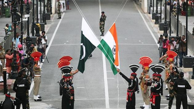 Pakistani Rangers (wearing black uniforms) and Indian Border Security Force (BSF) officers lower their national flags during parade on the Pakistan's 72nd Independence Day, at the Pakistan-India joint check-post at Wagah border, near Lahore, Pakistan.(Reuters/ File photo)