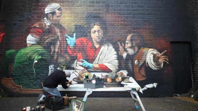 Artist Lionel Stanhope paints a mural in Ladywell depicting the Supper at Emmaus by Caravaggio with added protective gloves, following the outbreak of the coronavirus disease (Covid-19), London, Britain.(REUTERS)