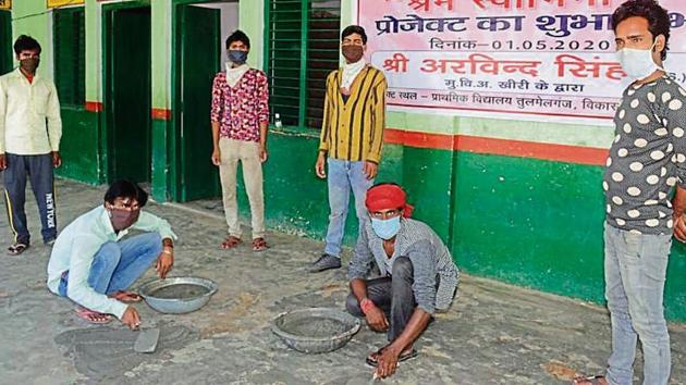 Migrants labourers engaged in repair works at a government-run primary school in Lakhimpur.(HT Photo)