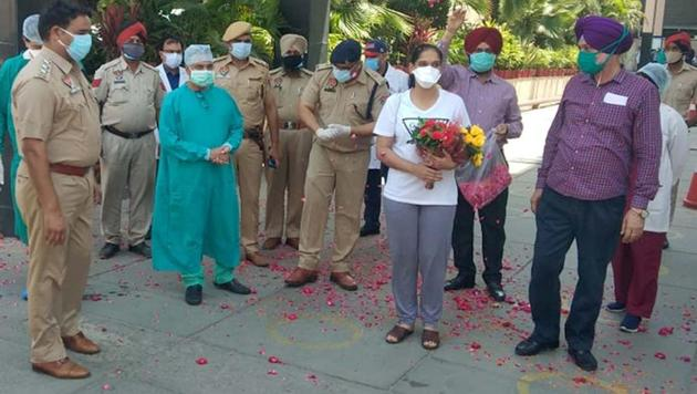 Sub-inspector Arshpreet Kaur receiving a floral welcome from the police department after being discharged from a hospital in Ludhiana on Friday.(HT Photo)