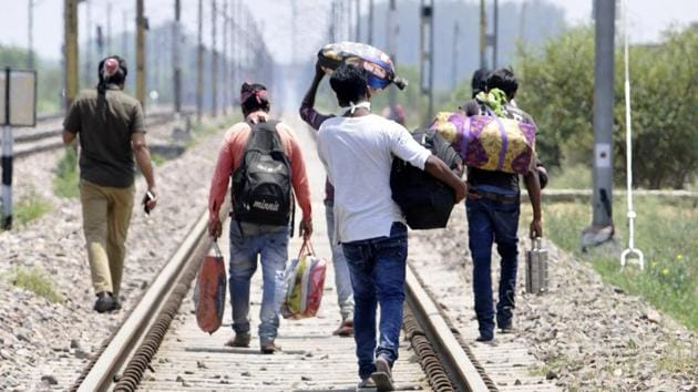 Migrants walking to their homes along a railway track in Greater Noida on Friday.(Sunil Ghosh/HT Photo)