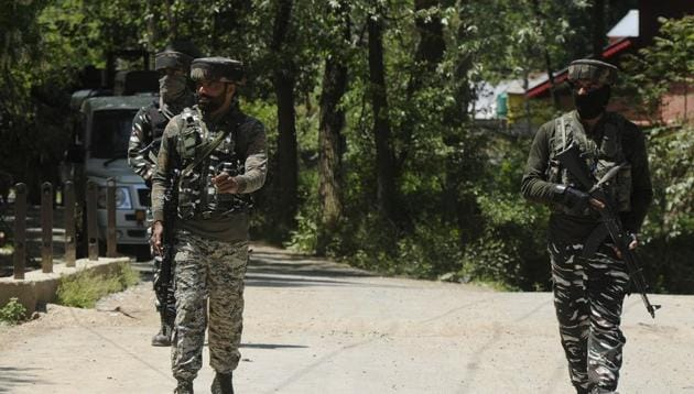 Security forces near the site of a gunfight in which Hizbul Mujahideen commander Riyaz Naikoo along with an associate were killed, in Beighpora area, Pulwama district, Jammu and Kashmir on Wednesday.(Waseem Andrabi/HT Photo)
