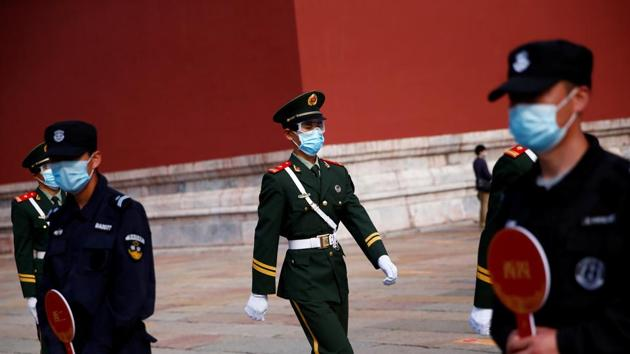 Paramilitary police officers and security guards wearing face masks are seen in China.(REUTERS)