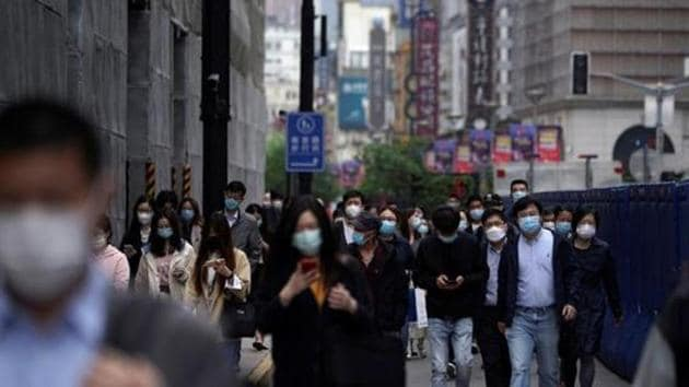 People wearing face masks walk at a main shopping area, following an outbreak of the novel coronavirus disease, in Shanghai, China.(REUTERS)