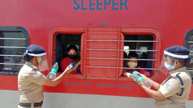 Police personnel distribute water bottles to passengers leaving for Bankura in West Bengal, on a special train, in Bengaluru on Sunday.(ANI)