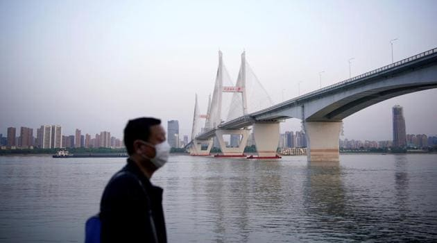 A man wearing a face mask is seen under a bridge of Yangtze river in Wuhan after the lockdown was lifted, on April 15.(Reuters File Photo)