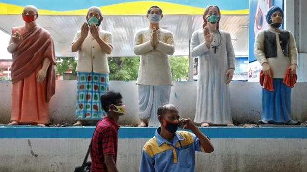 Men wearing protective masks move past the figures with face masks installed outside a fuel station to create awareness about wearing masks to prevent the spreading of the coronavirus disease (COVID-19), in Kolkata, India.(REUTERS)
