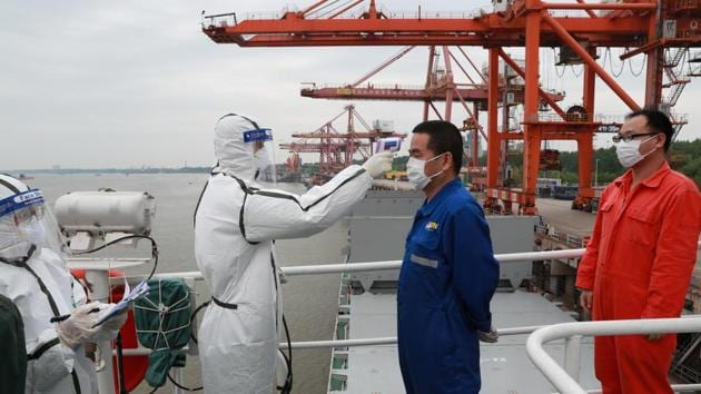 A staff member in protective suit takes body temperature measurement of a crew worker of a cargo ship bound for Japan following the coronavirus disease (Covid-19) outbreak, at a container terminal at a port in Wuhan, Hubei province, China.(REUTERS)