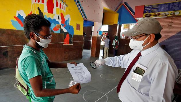 A railway officer uses a magnifying glass to check the travel document of a man upon his arrival at a railway station to board a train to New Delhi after a limited reopening of India's rail network on May 12.(Reuters Photo)