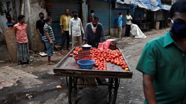A food vendor selling tomatoes on the street, pushes along his cart, during a nationwide lockdown in India to slow the spread of Covid-19, in Dharavi.(Reuters file photo)