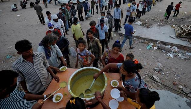 Migrant workers and homeless people stand in queue to receive free food during a nationwide lockdown to curb the spread of the coronavirus disease in India.(REUTERS PHOTO.)