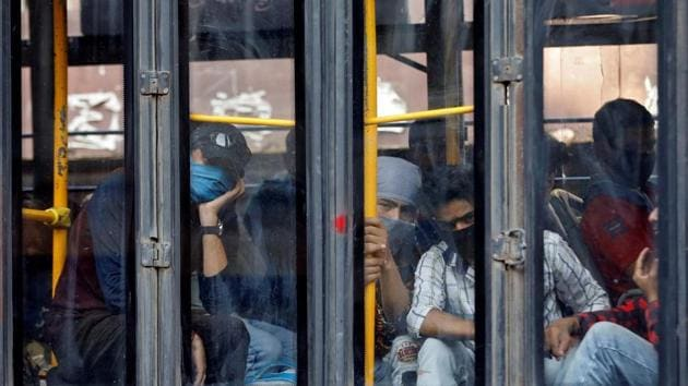 Migrant workers look out from a bus as they wait to enter a railway station to board a train to reach their home state of Uttarakhand, after a limited reopening of India's giant rail network following a nearly seven-week lockdown to slow the spreading of the coronavirus disease.(REUTERS)