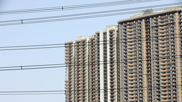 Housing stands beyond electricity lines near the Indirapuram township in Ghaziabad.(Bloomberg)