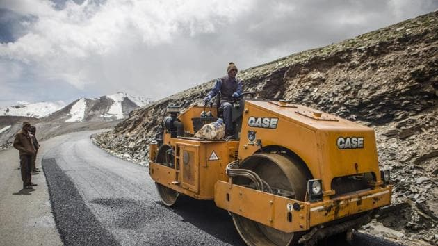 A Border Roads Organisation (BRO) worker drives a steamroller while repairing a road surface with tarmac on a section of the Leh Manali highway in Ladakh region.(Photographer: Prashanth Vishwana)