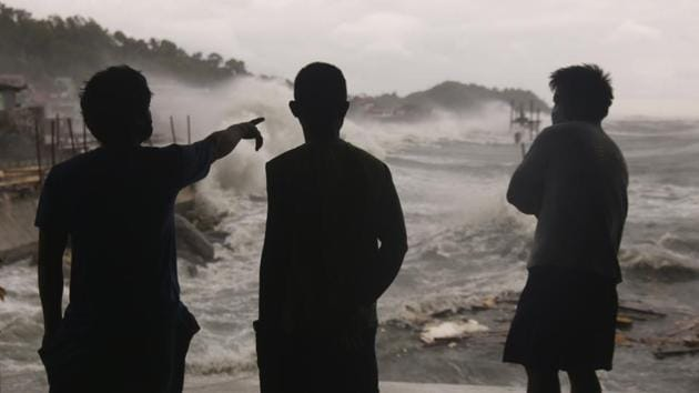 Men watch as strong waves caused by Typhoon Vongfong batter the coastline of Catbalogan city. It's expected to traverse several northern provinces before heading back to sea over the weekend and then probably dissipate on Monday. (Simvale Sayat / AP)