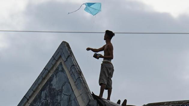 A resident flies a kite atop his house inside a tenement building in Manila. Vongfong is packing maximum sustained winds of 125 kilometers per hour (78 miles) near the centre and gusts of up to 165 kph while traversing the eastern part of the country, the Philippine Atmospheric, Geophysical and Astronomical Services Administration said on Friday, as reported Bloomberg. (Ted ALjibe / AFP)