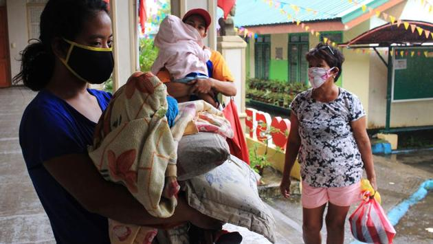 Residents carrying their belongings and wearing face masks, arrive at a school compound serving as temporary shelter in Sorsogon town. In the northeastern Bicol region, more than 145,000 villagers fled or were moved by disaster-response teams to dozens of emergency shelters, mostly school buildings. (Sharbyn Sayat / AFP)